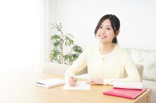 自宅で勉強をする若い女性の写真素材 [FYI04657095]