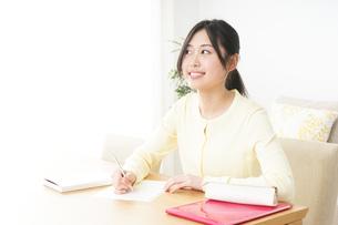 自宅で勉強をする若い女性の写真素材 [FYI04657097]