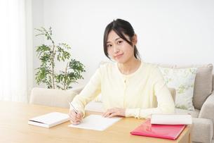 自宅で勉強をする若い女性の写真素材 [FYI04657099]