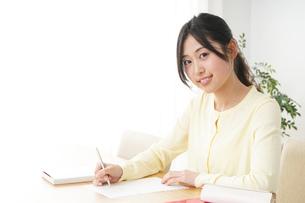 自宅で勉強をする若い女性の写真素材 [FYI04657100]