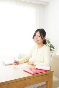 自宅で勉強をする若い女性の写真素材 [FYI04657101]