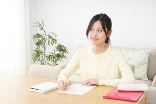 自宅で勉強をする若い女性の写真素材 [FYI04657102]