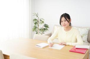 自宅で勉強をする若い女性の写真素材 [FYI04657104]