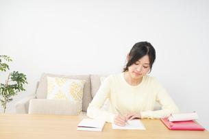 自宅で勉強をする若い女性の写真素材 [FYI04657105]