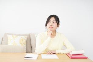 自宅で勉強をする若い女性の写真素材 [FYI04657106]