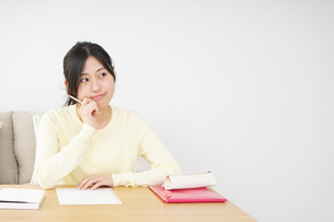 自宅で勉強をする若い女性の写真素材 [FYI04657107]