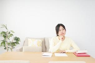 自宅で勉強をする若い女性の写真素材 [FYI04657108]