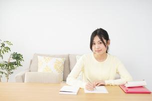 自宅で勉強をする若い女性の写真素材 [FYI04657109]