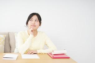 自宅で勉強をする若い女性の写真素材 [FYI04657110]