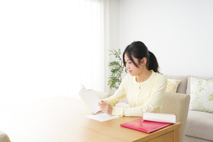 自宅で勉強をする若い女性の写真素材 [FYI04657111]