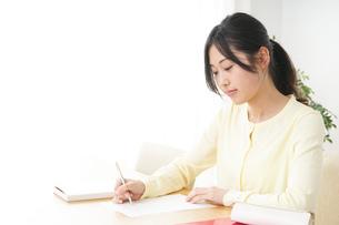 自宅で勉強をする若い女性の写真素材 [FYI04657112]