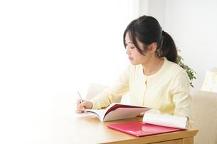 自宅で勉強をする若い女性の写真素材 [FYI04657114]