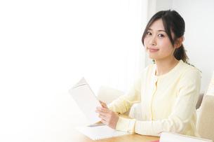 自宅で勉強をする若い女性の写真素材 [FYI04657115]