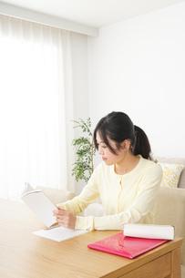 自宅で勉強をする若い女性の写真素材 [FYI04657116]