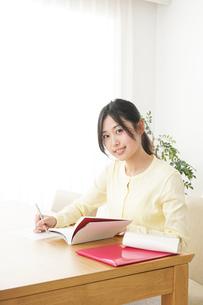 自宅で勉強をする若い女性の写真素材 [FYI04657118]