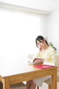 自宅で勉強をする若い女性の写真素材 [FYI04657120]