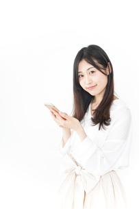 笑顔でスマホを使う若い女性の写真素材 [FYI04657395]