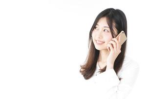 笑顔でスマホを使う若い女性の写真素材 [FYI04657402]