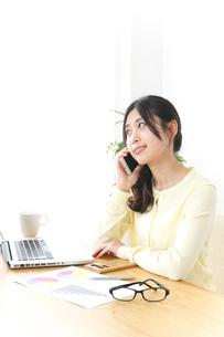 オフィスで電話をするビジネスウーマンの写真素材 [FYI04657442]