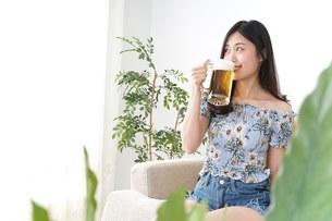 自宅でビールを飲む女性の写真素材 [FYI04657490]