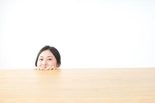 テーブルから顔を出す女性の写真素材 [FYI04657548]