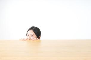 テーブルから顔を出す女性の写真素材 [FYI04657550]