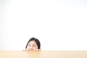 テーブルから顔を出す女性の写真素材 [FYI04657551]