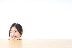 テーブルから顔を出す女性の写真素材 [FYI04657556]