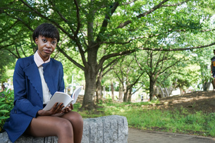 公園で読書をする黒人女性の写真素材 [FYI04657628]