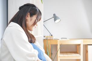 部屋でリラックスする女性の写真素材 [FYI04657873]