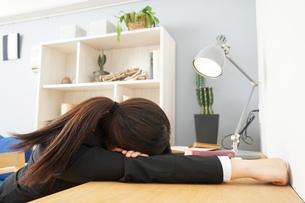 スーツを着て机で寝る女性の写真素材 [FYI04657975]