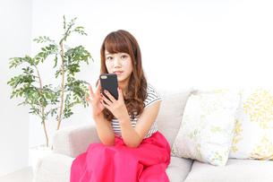 部屋でスマホを使う女性の写真素材 [FYI04658610]