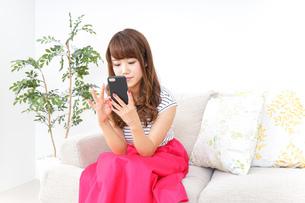 部屋でスマホを使う女性の写真素材 [FYI04658611]