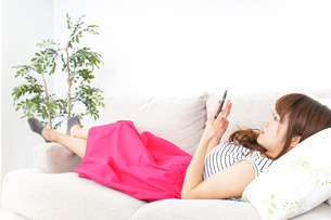 部屋でスマホを使う女性の写真素材 [FYI04658618]