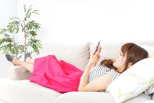 部屋でスマホを使う女性の写真素材 [FYI04658619]