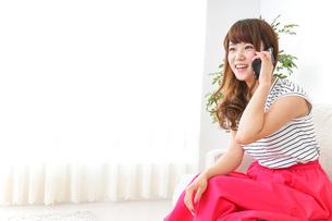 部屋でスマホを使う女性の写真素材 [FYI04658625]