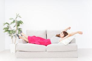 ソファで寝る若い女性の写真素材 [FYI04658718]