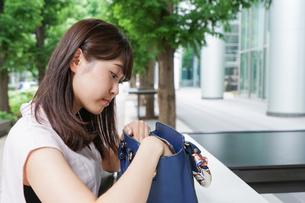カバンを見る若い女性の写真素材 [FYI04658820]