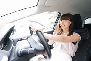 スマホを使いながら運転する女性の写真素材 [FYI04658826]