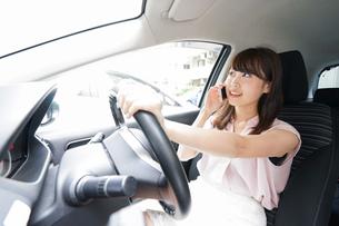 スマホを使いながら運転する女性の写真素材 [FYI04658830]