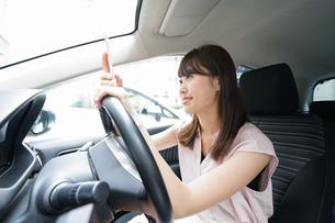 スマホを使いながら運転する女性の写真素材 [FYI04658834]