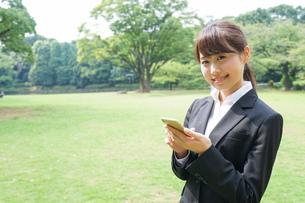 メッセージを確認するスーツ姿の女性の写真素材 [FYI04658871]