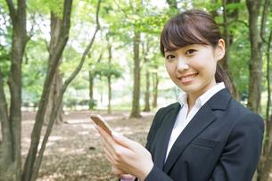 メッセージを確認するスーツ姿の女性の写真素材 [FYI04658875]