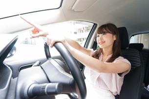 指をさす女性ドライバーの写真素材 [FYI04659063]