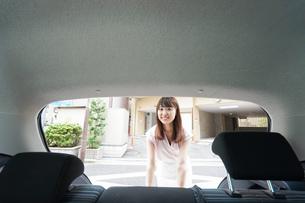 車のトランクを開ける女性の写真素材 [FYI04659188]