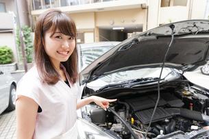 車のメンテナンスをする女性の写真素材 [FYI04659199]