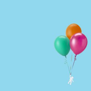 風船を手に持って飛んでいる人の写真素材 [FYI04659902]