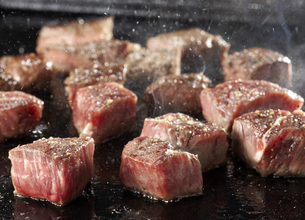 Cooking dice steak on iron hot plateの写真素材 [FYI04663622]