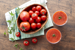 Tomato and tomato juice on a wooden tableの写真素材 [FYI04664656]