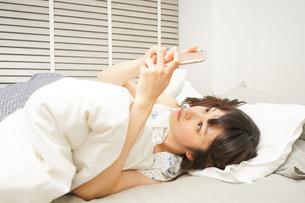 寝る前に携帯を使う若い女性の写真素材 [FYI04665839]